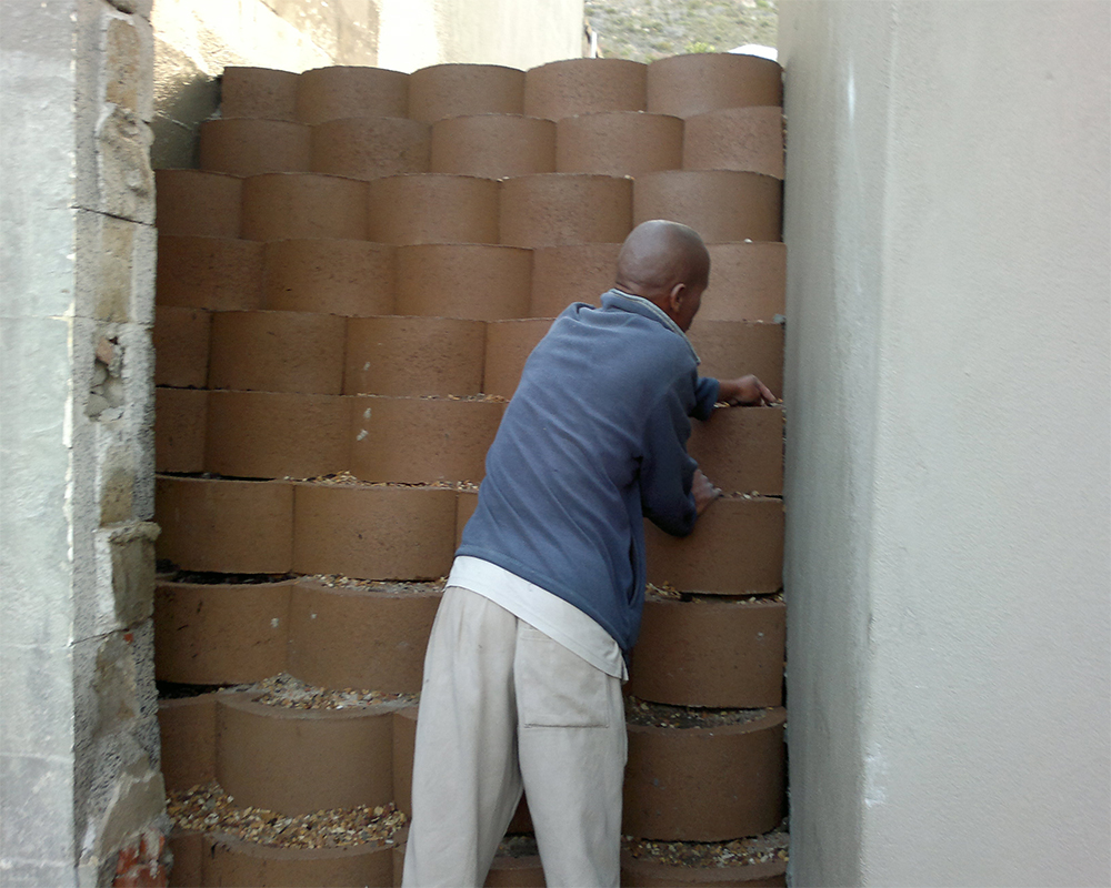 Hambisela-Horticultural_Service_House-Gabier---Fish-Hoek---Pendu-busy-filling-retaining-blocks-to-stabilise-wall-with-sand-and-stone